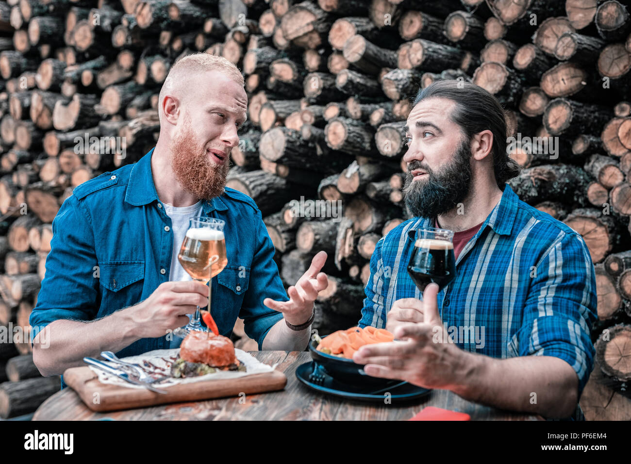 Two bearded businessmen having informal meeting drinking beer - Stock Image