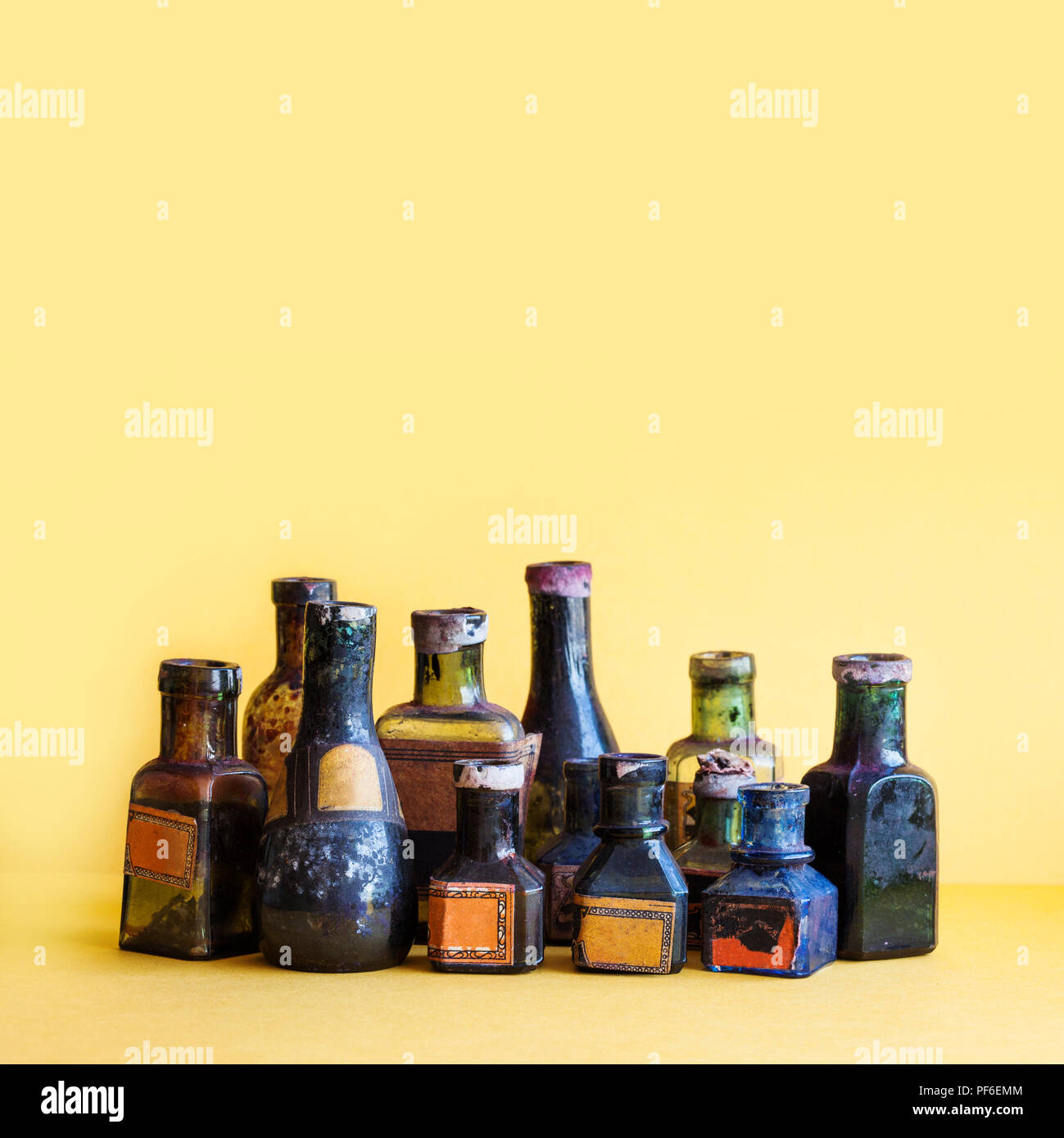 Vintage bottles close-up. Colorful dirty glass flacon set. Soft yellow background, shallow depth of field. copy space - Stock Image