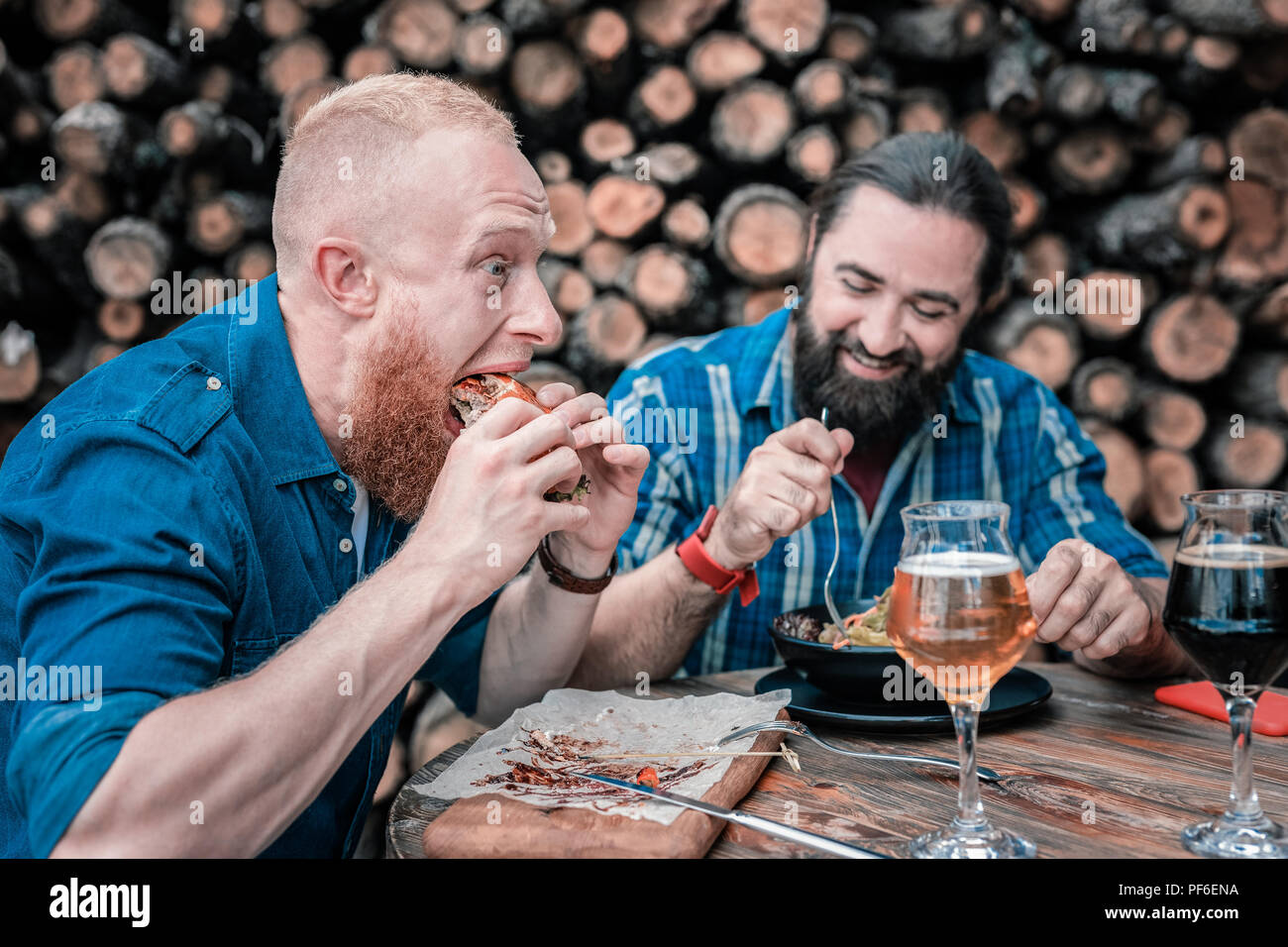 Red-haired man eating junk food sitting hear his friend with salad - Stock Image