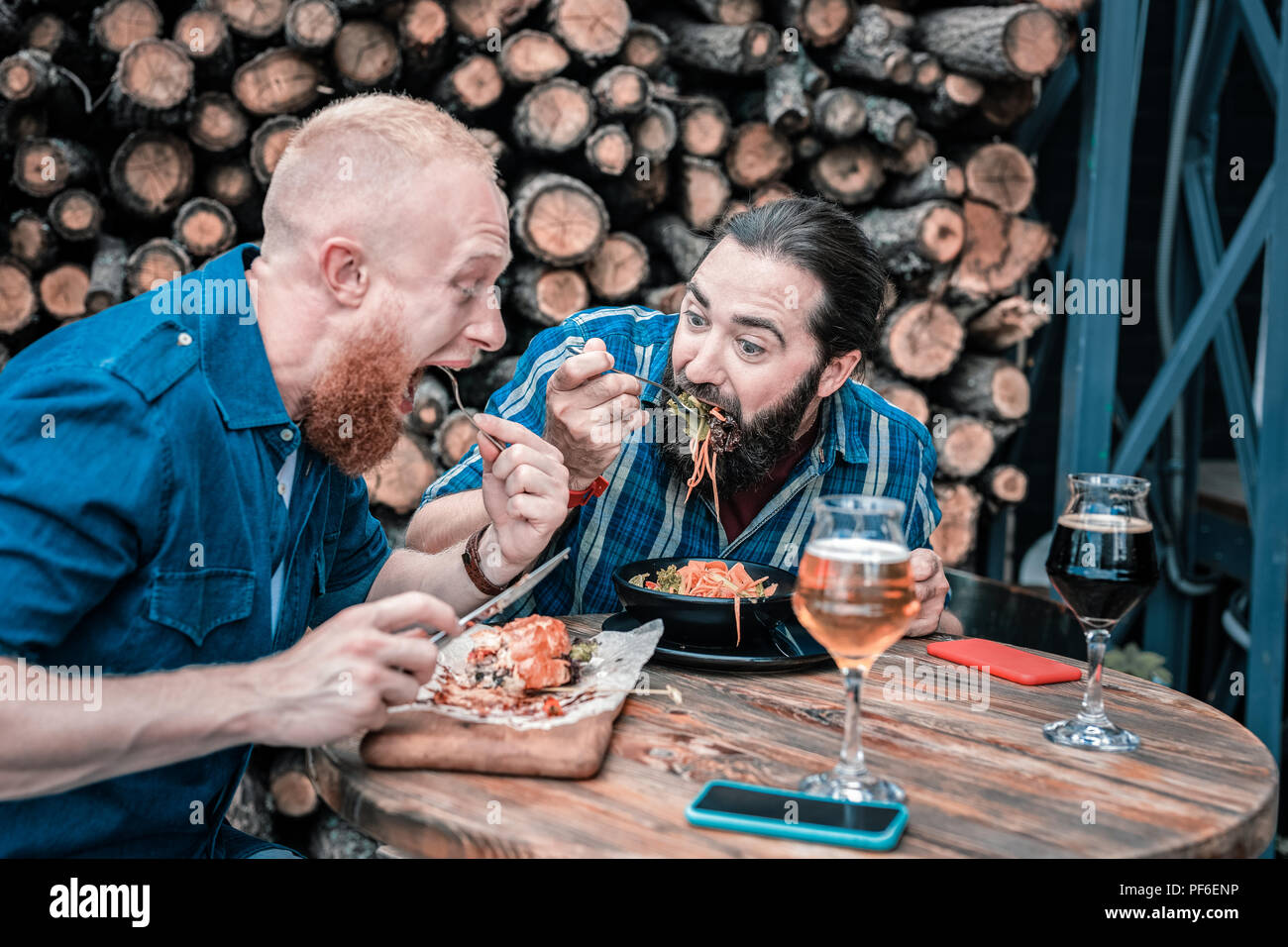 Two hungry men feeling good while having tasty dinner - Stock Image