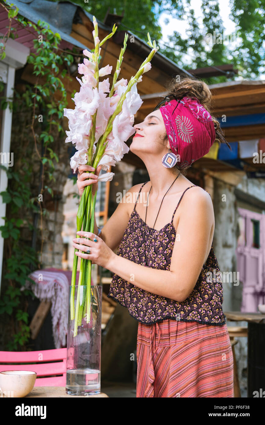 Creative female hippie smelling nice white flowers - Stock Image