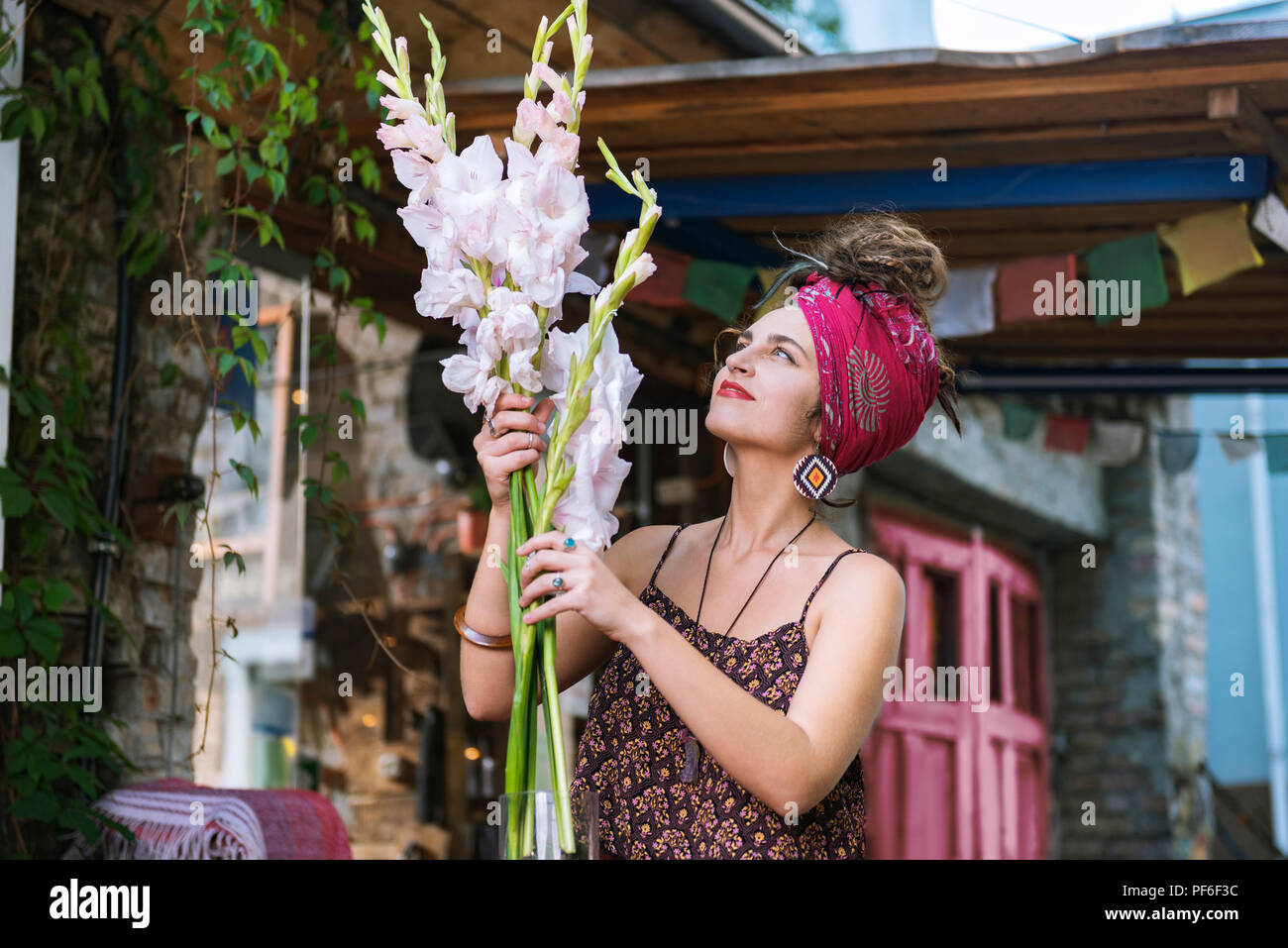 Dark-haired woman wearing red headband looking at flowers - Stock Image