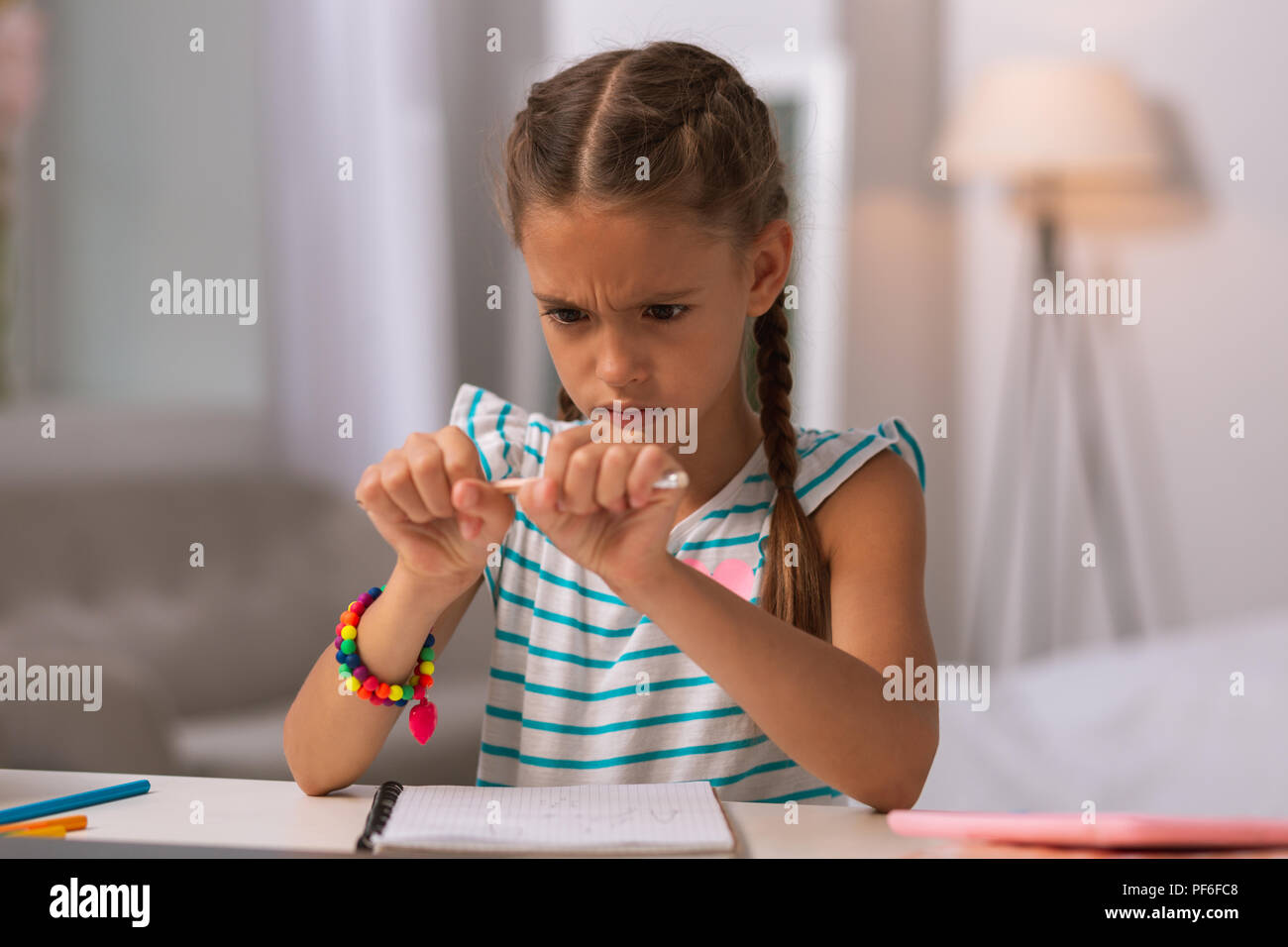 Depressed angry girl holding a pencil at home - Stock Image