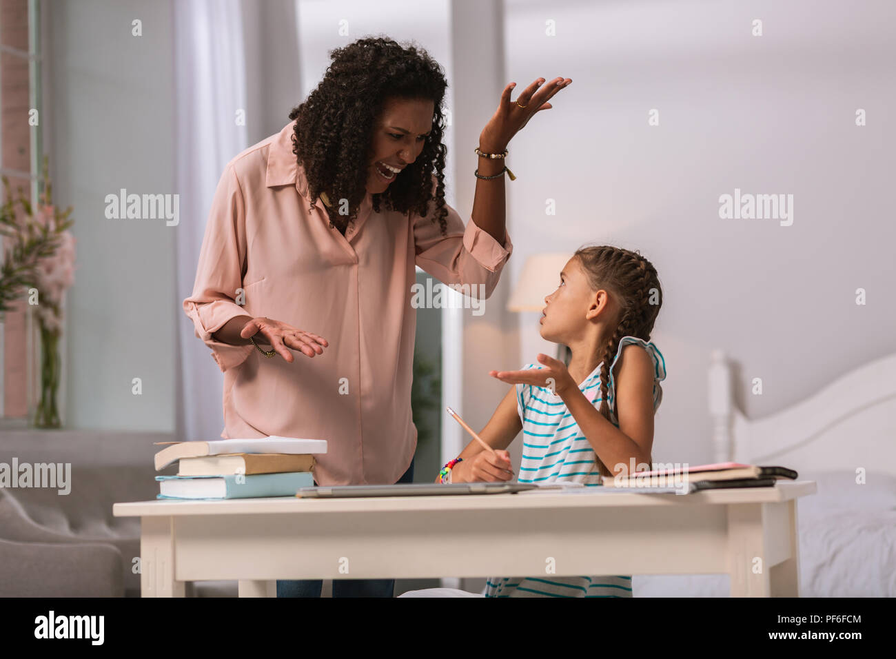 Cheerless angry woman being unhappy with her daughter - Stock Image