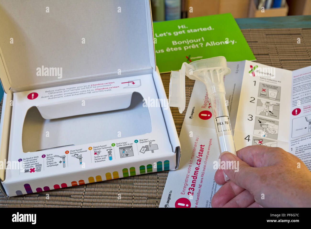 23andme home genetic testing kit.  Person holding saliva collection tube with the rest of the kit. - Stock Image