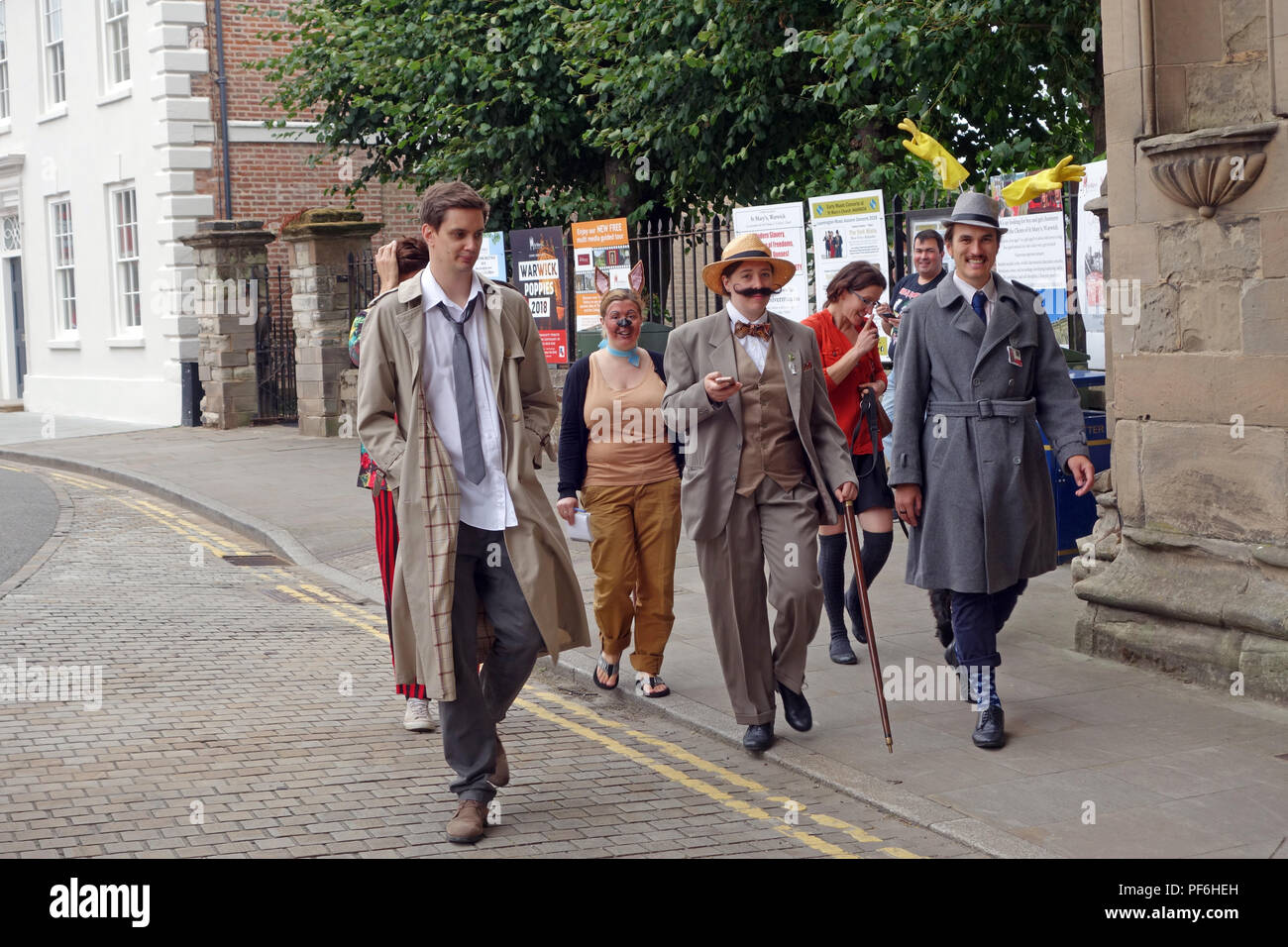 Group of wannabe detectives all wearing fancy dress on a virtual Murder Mystery daytime event on the streets of Warwick England - Stock Image