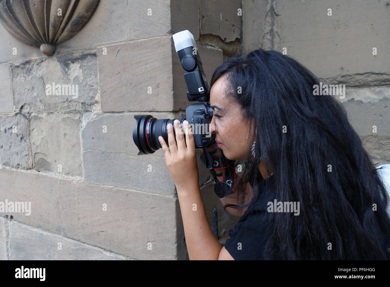Side view of Female professional photographer using her camera and flash gun at a wedding - Stock Image