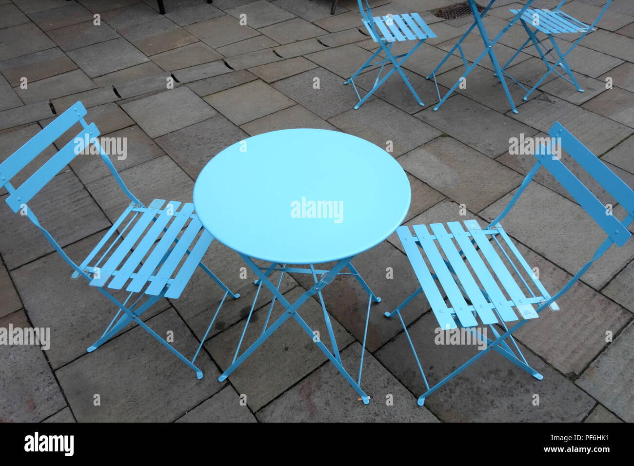 Round blue table and chairs at a Weekly Saturday market with many stalls is held in Warwick town centre, Warwickshire, England - Stock Image