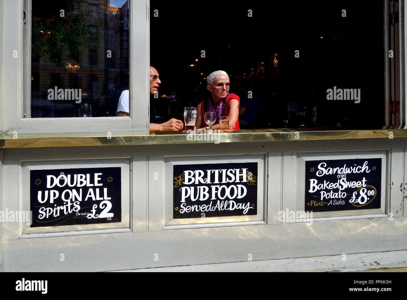 People at the open window of The Garrick Arms pub in Charing Cross Road, London, England, UK. - Stock Image