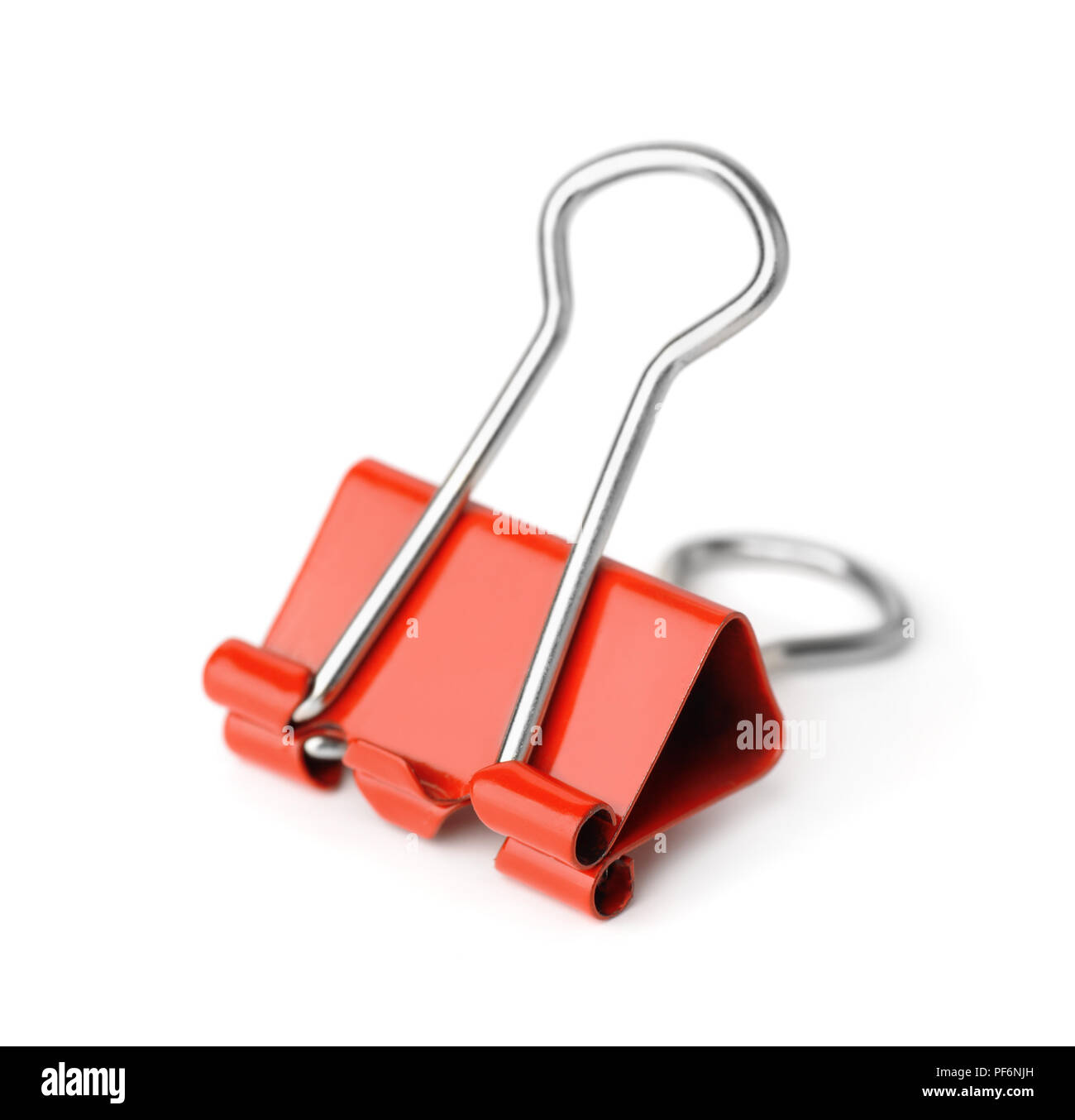 Red metal binder clip isolated on white - Stock Image