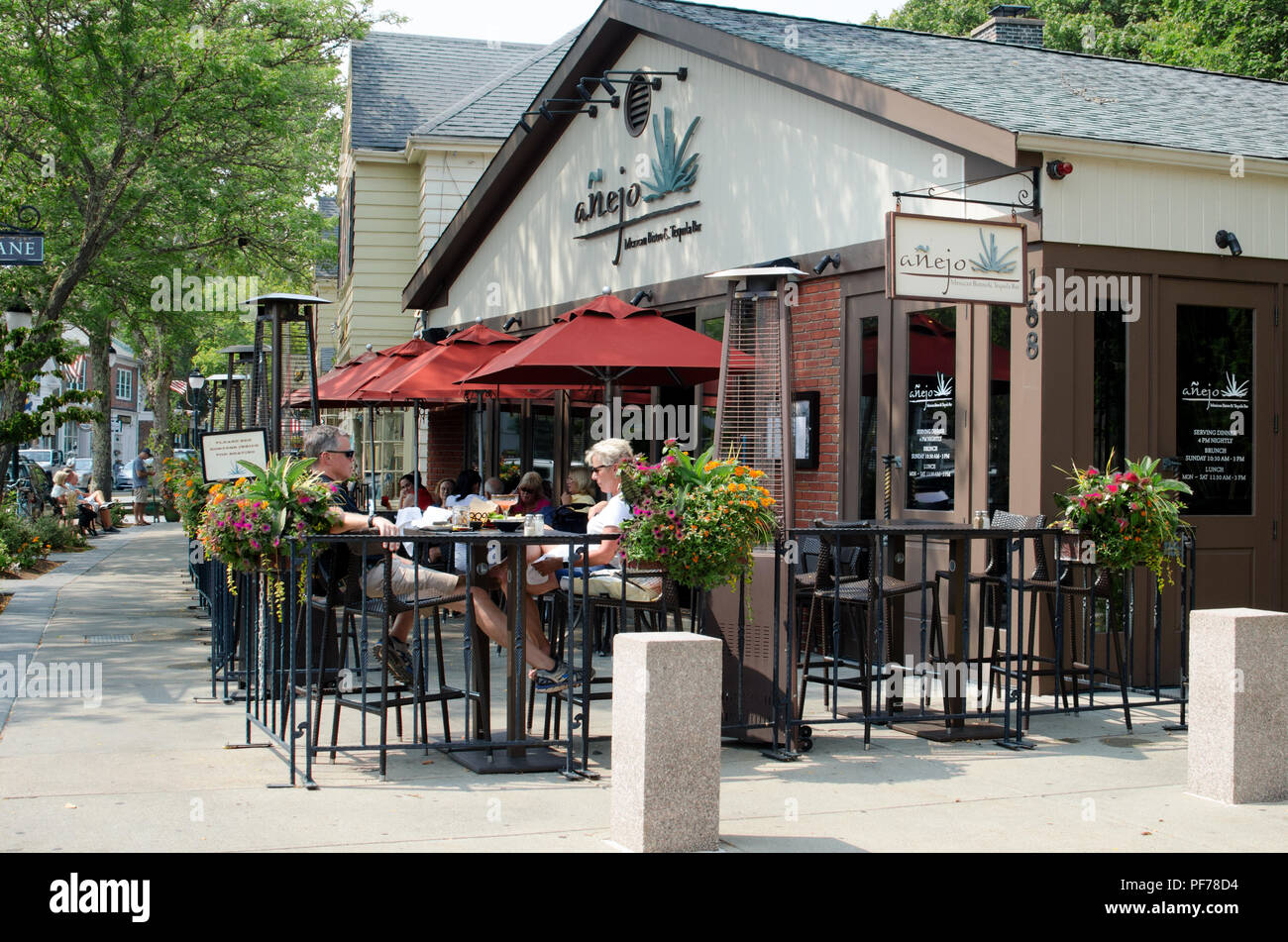 Downtown Falmouth, Cape Cod Massachusetts USA with people dining outdoors at Anejo Mexican restaurant and people walking on sidewalk - Stock Image