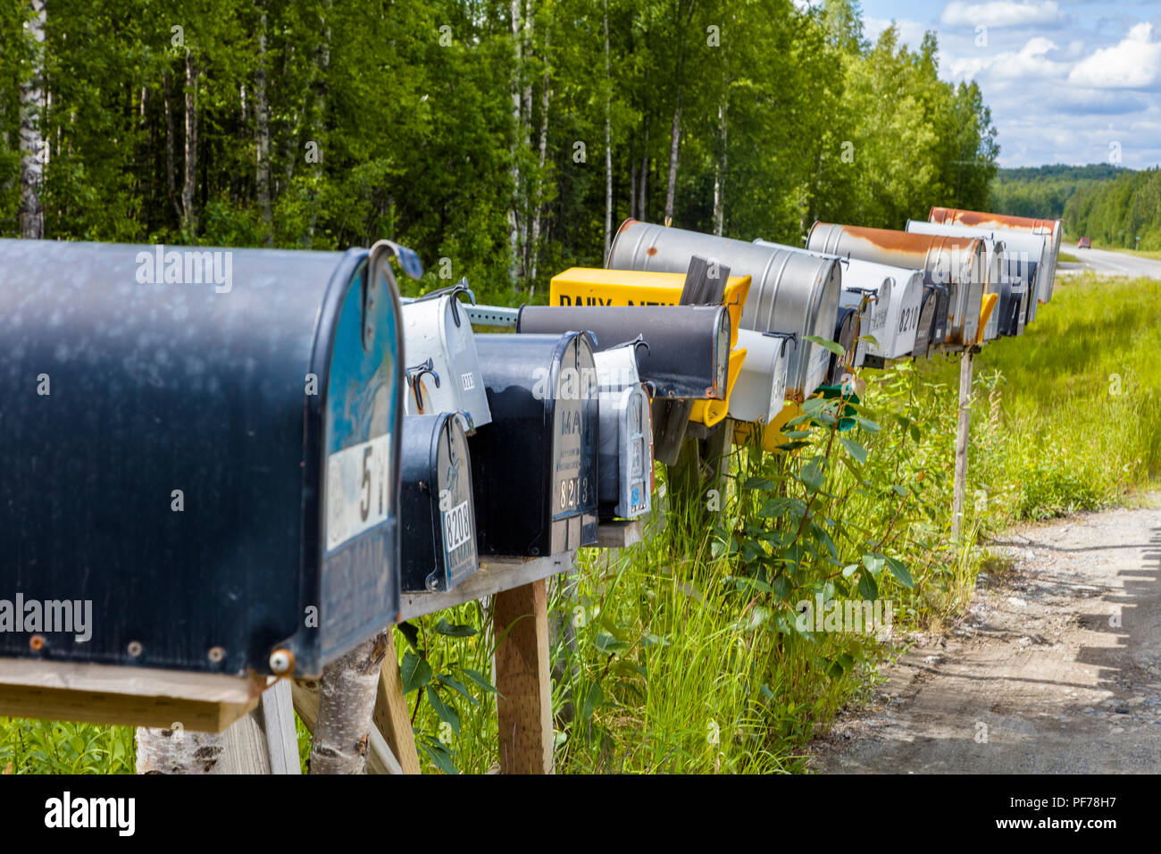 Line of mailboxes along side road - Stock Image