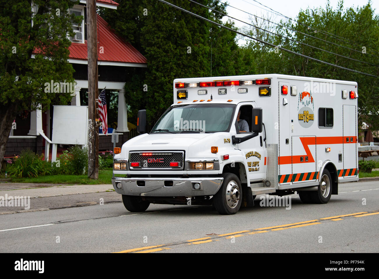 The Volunteer Fire Department emergency rescue vehicle racing through Speculator, NY USA responding to an emergency with lights flashing. - Stock Image
