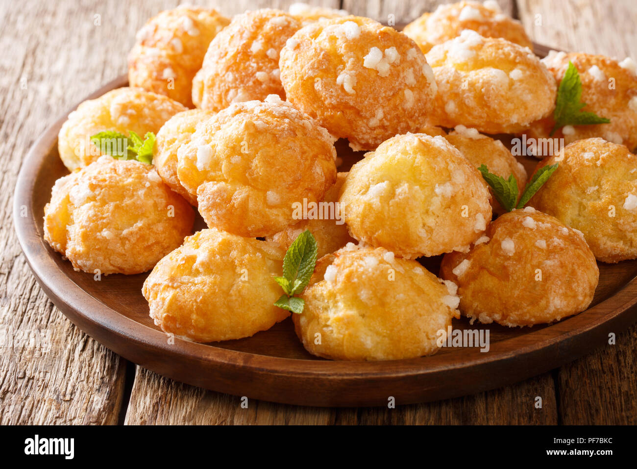 French heap Cream Puffs choux with pearl sugar and mint macro on a plate on a table. Horizontal - Stock Image