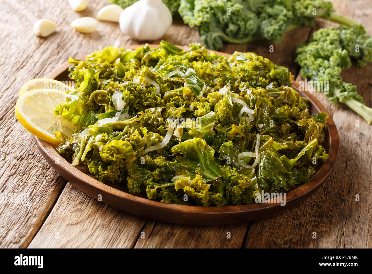 Kale or leaf cabbage cooked with onions, garlic, olive oil and lemon close-up on a plate on a table. horizontal - Stock Image
