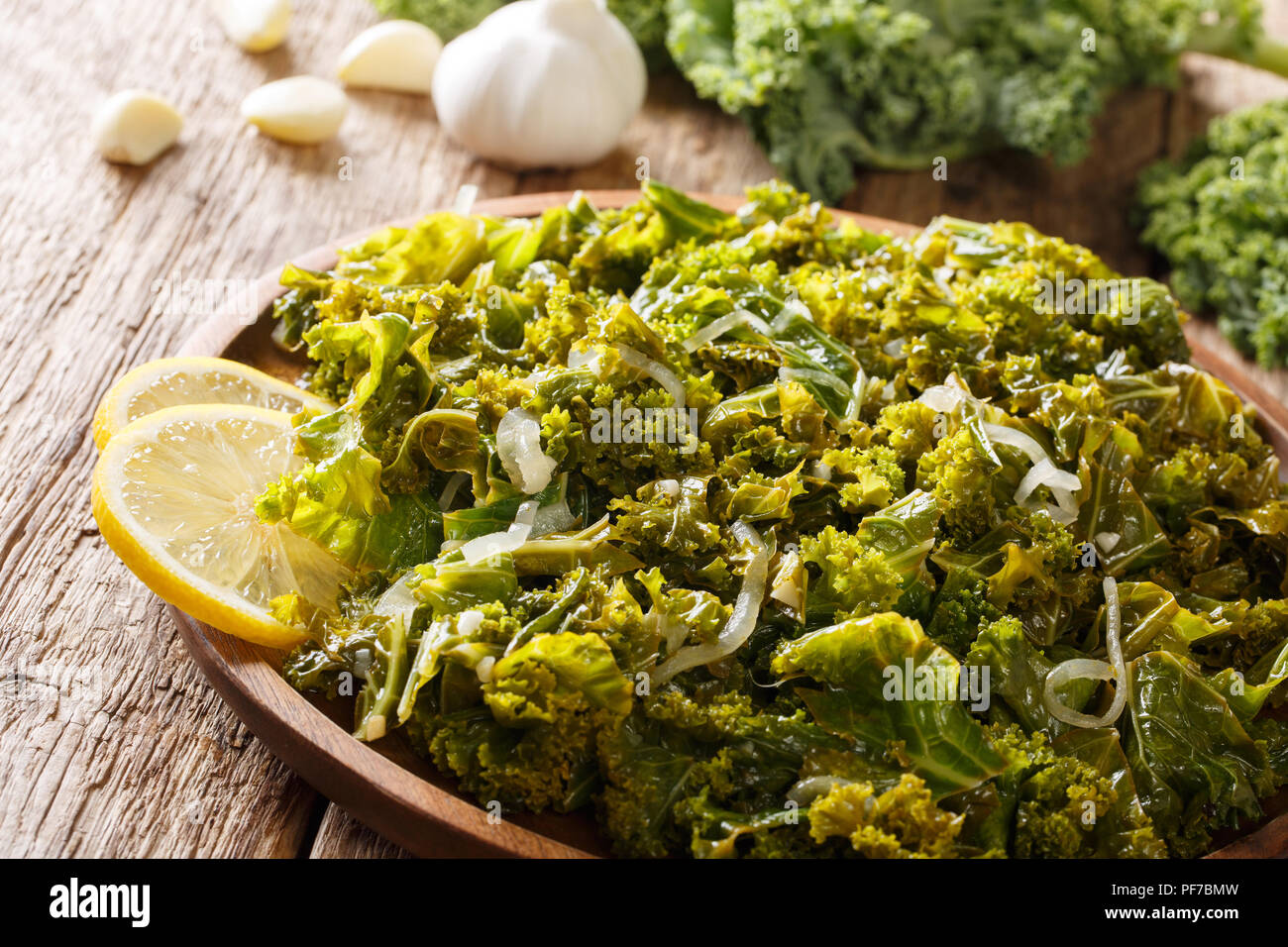 Delicious kale, onions, garlic and lemon close-up on a plate and ingredients on the table. horizontal - Stock Image