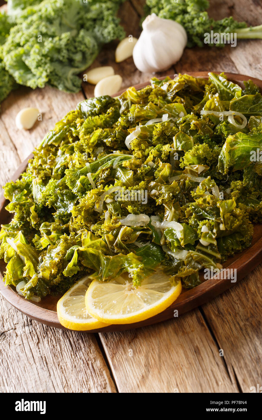 Vegan meal: stewed kale cabbage with onions and garlic and lemon close-up on a plate. vertical - Stock Image