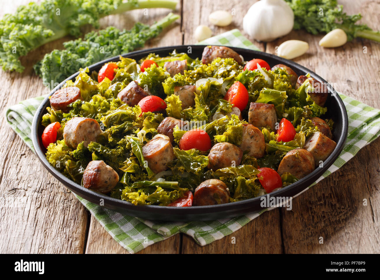 kale with grilled sausages, fresh tomatoes and garlic close-up on a plate on a table. horizontal - Stock Image