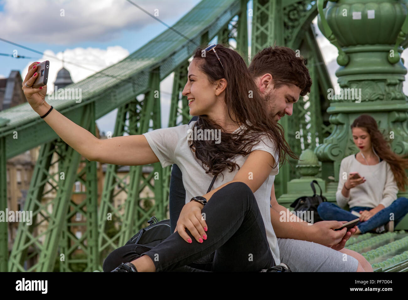 Young couple taking selfie on the famous Liberty Bridge,known as Freedom,or even Green bridge in Budapest,reading  young girl on the background - Stock Image