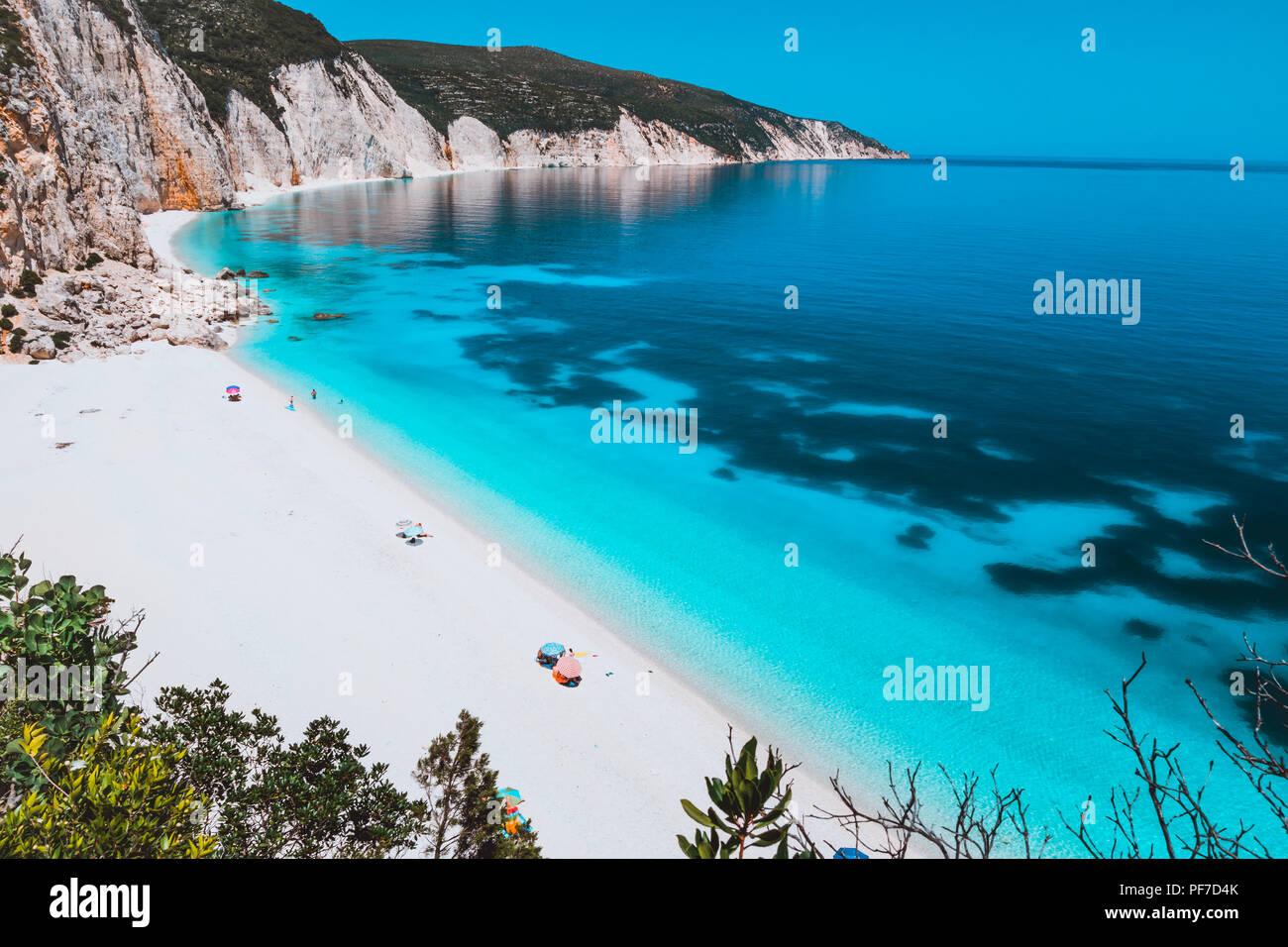 Sunny idyllic Fteri beach lagoon with limestone rocky coastline, Kefalonia, Greece. Tourists relax under umbrella near clear blue emerald turquoise sea water with dark pattern on bottom Stock Photo
