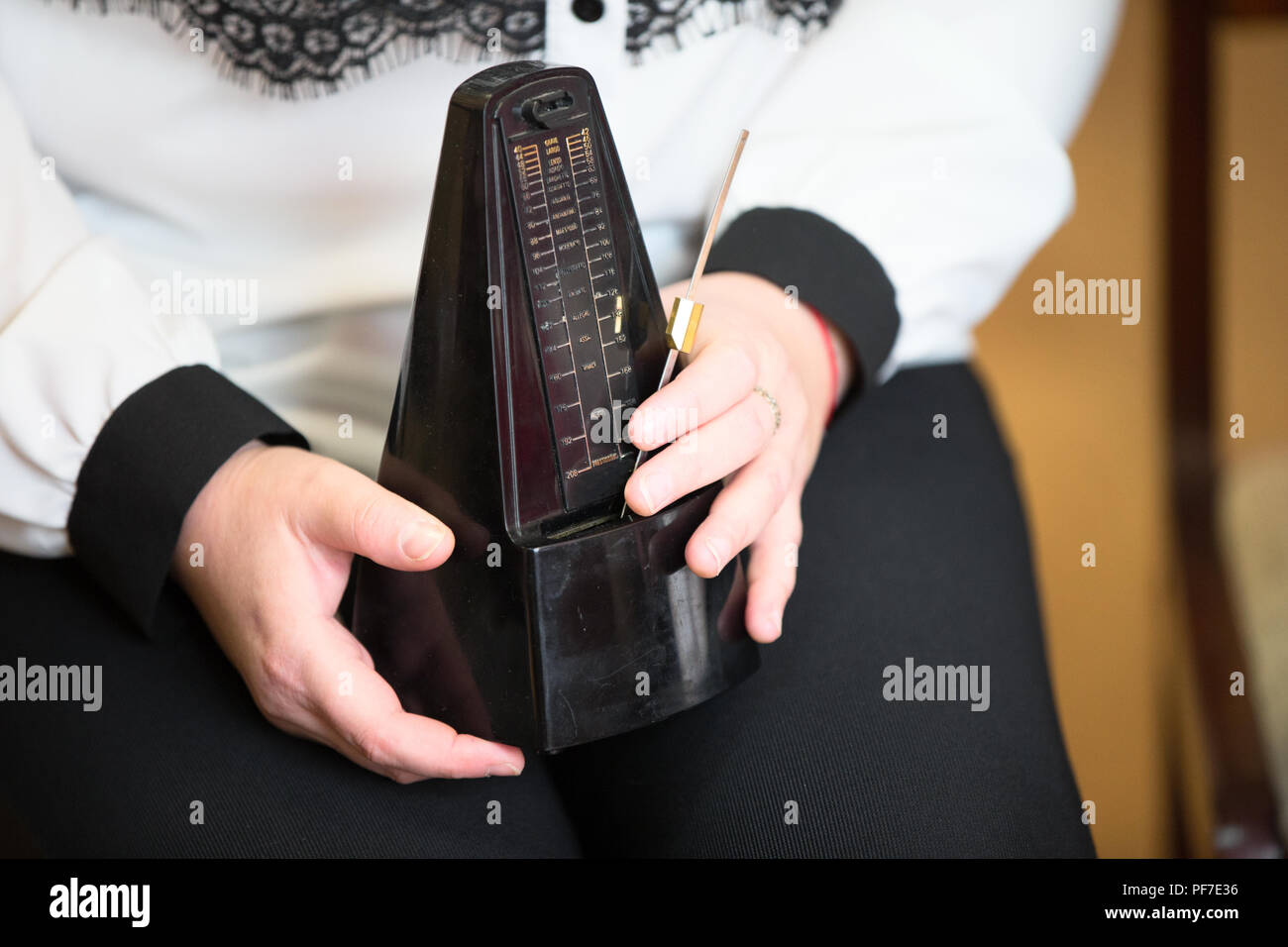 Hands hold a musical metronome - Stock Image