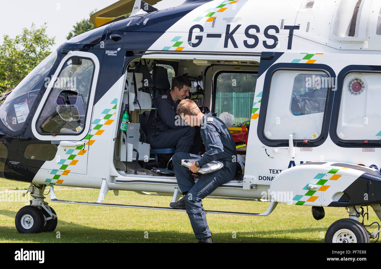 Surrey & Sussex air ambulance helicopter (G-KSST) on the ground with staff chatting, in West Sussex, England, UK. Aircraft is AgustaWestland AW169. - Stock Image