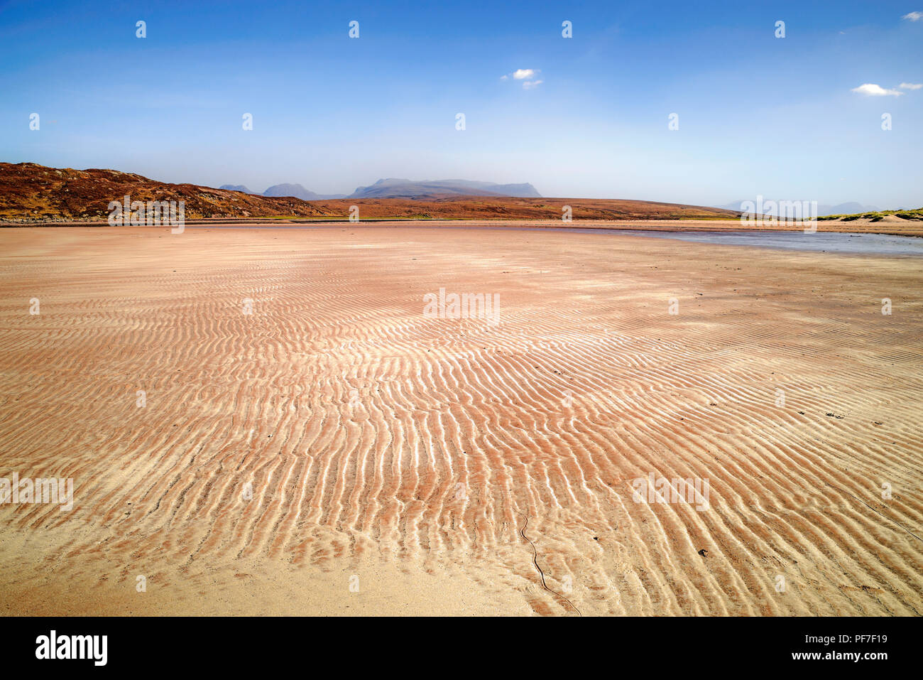 Sand ripples on beautiful remote sandy beach, Achnahaird Bay, Coigach, Wester Ross, Scottish Highlands, Ben More Coigach visible on hazy horizon. - Stock Image