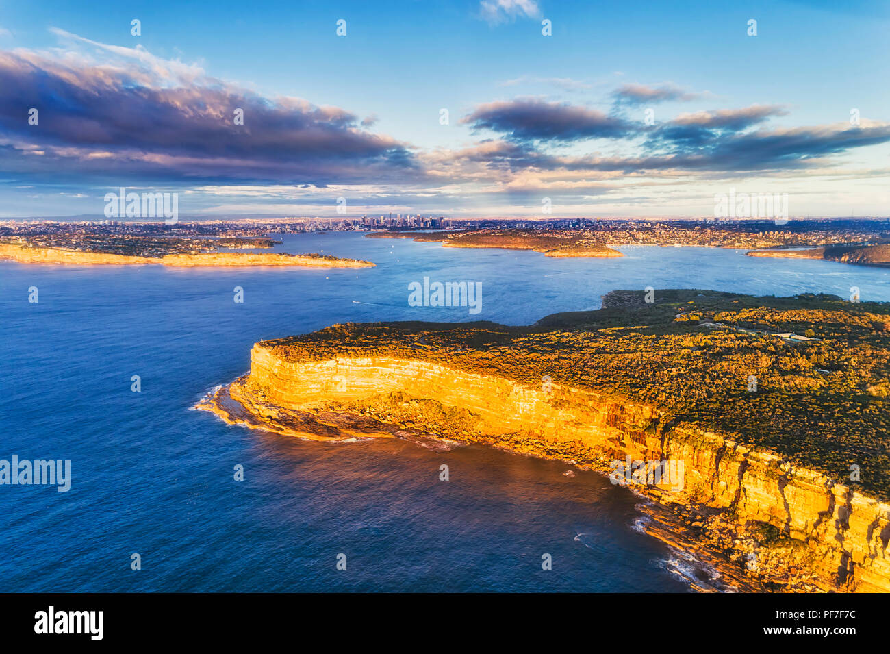 Steep edge of Sydney's north head sandstone cliffs facing Pacific ocean at the entrance to Sydney harbour in aerial elevated view towards city CBD. - Stock Image