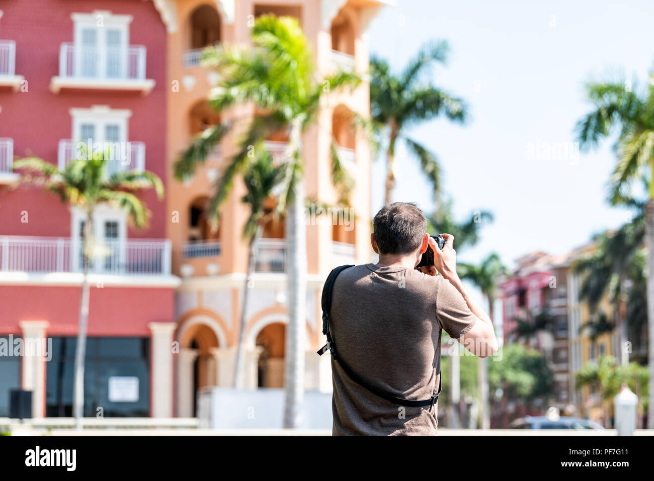 Closeup of young man photographer, photographing, taking pictures of colorful multicolored buildings in Florida or Spain during sunny day, condos, con - Stock Image