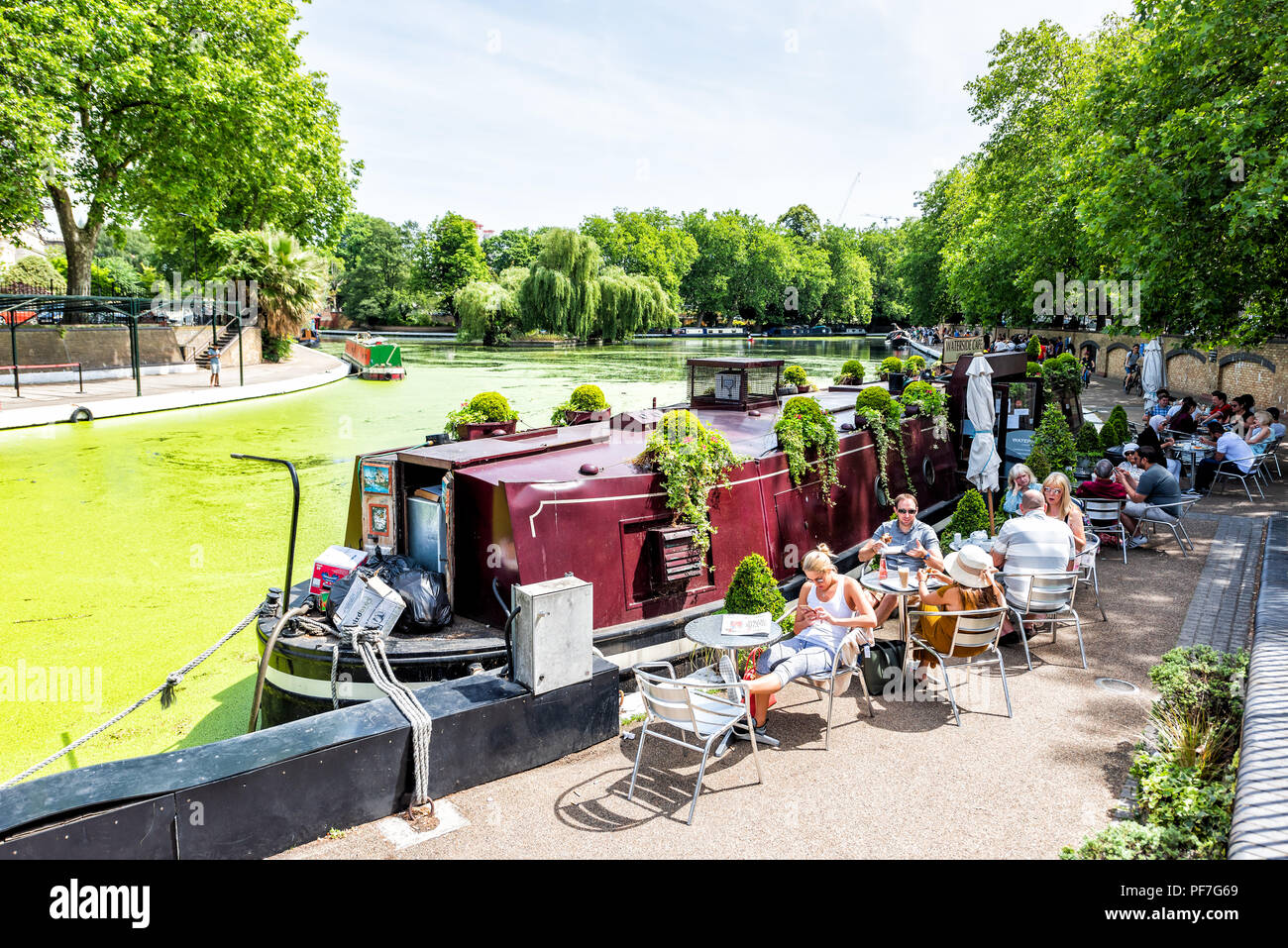 London, UK - June 24, 2018: Neighborhood district of Little Venice Italy, sidewalk canal cafe restaurant traditional style boat, people eating during  - Stock Image