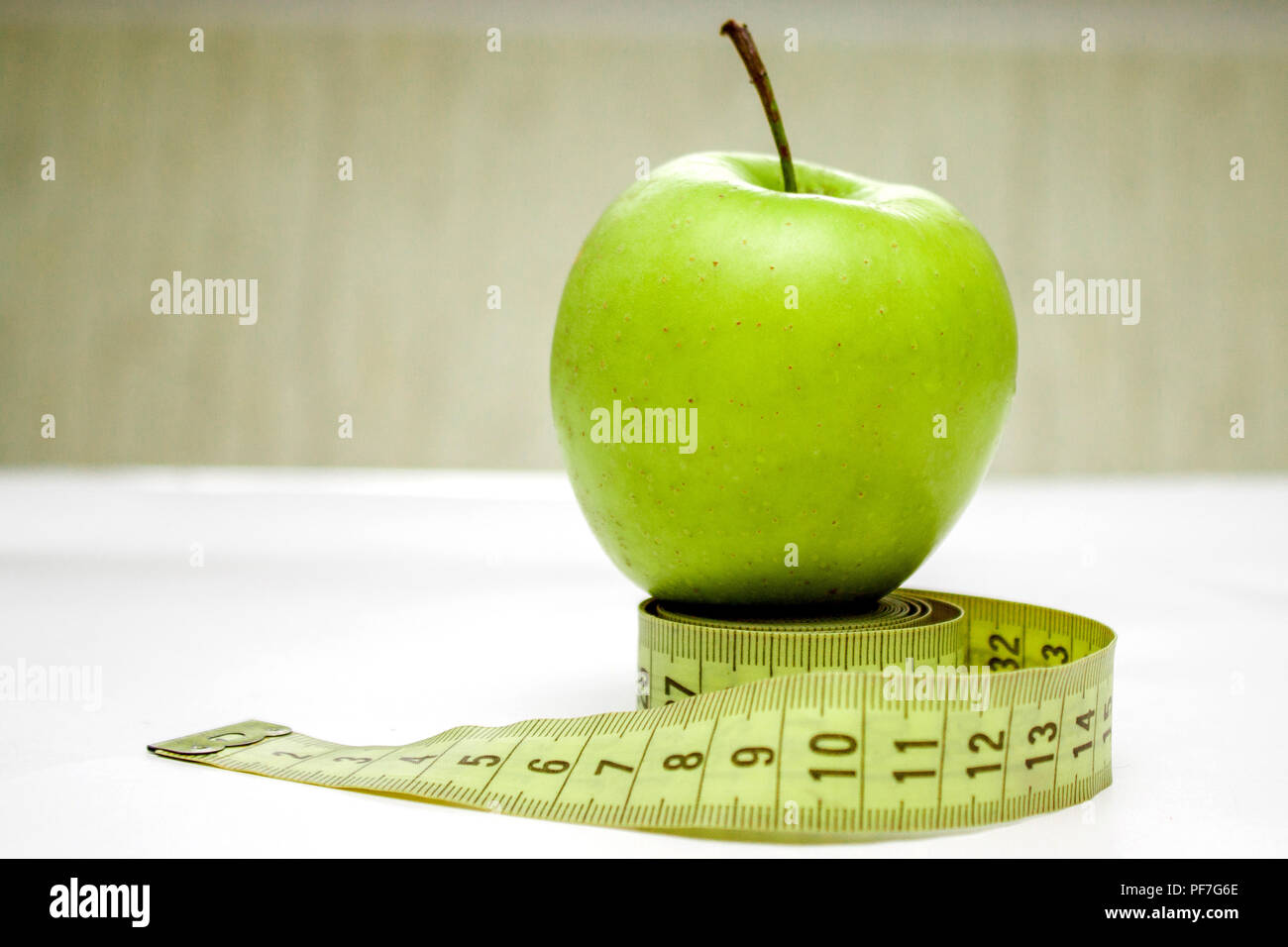 Diet, healthy eating, food and weigh loss concept. Measuring tape and green apple Stock Photo