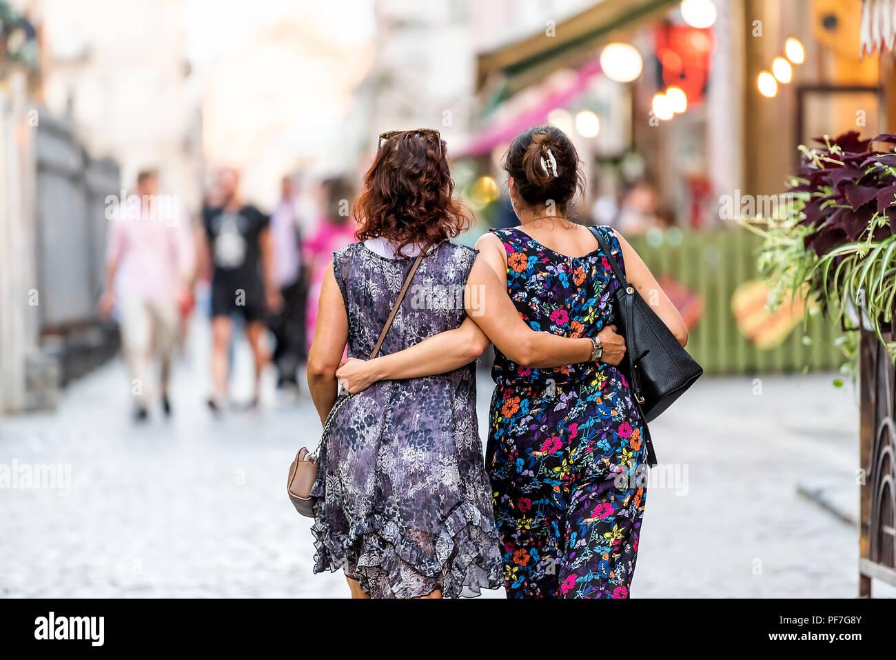 Lviv, Ukraine - July 30, 2018: Two Slavic Eastern European Ukrainian women walking back with arms around each other hugging holding in historic Ukrain - Stock Image
