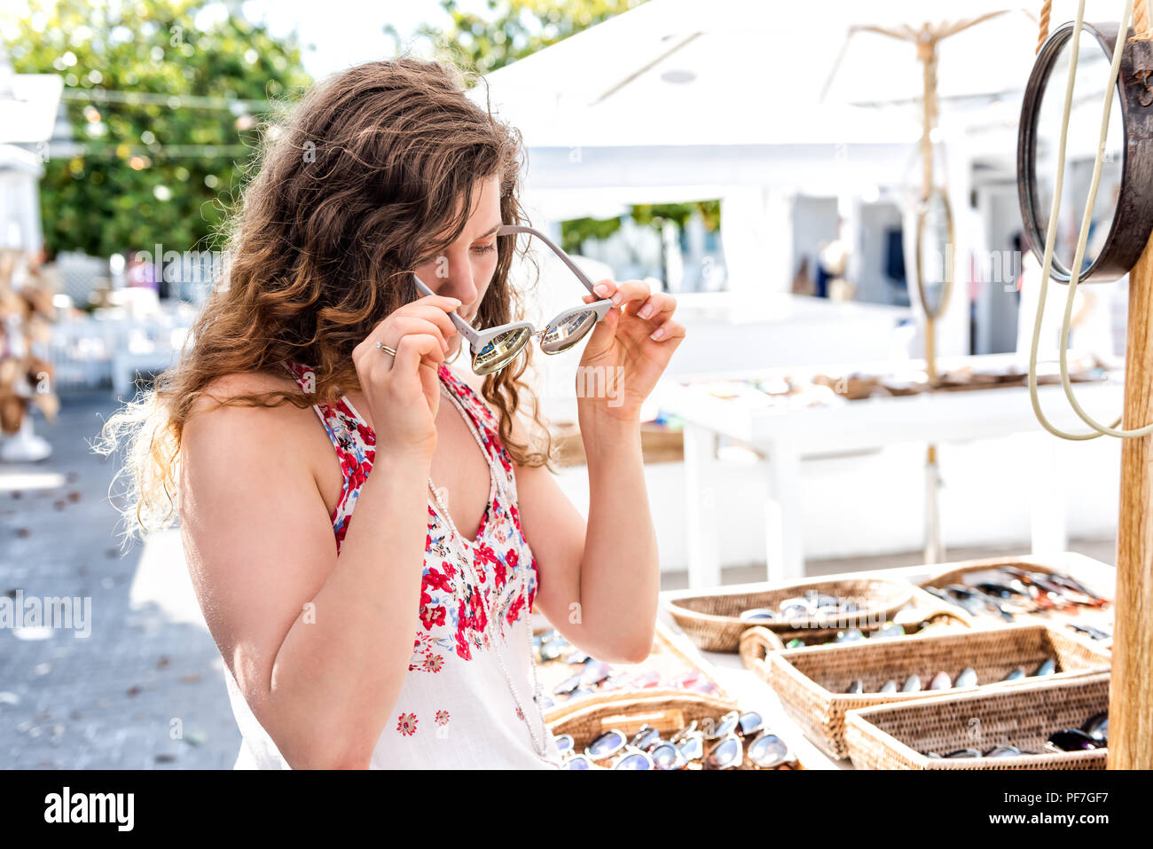 Closeup of young woman shopping for modern sunglasses trying on in outdoor market shop store in European, Greece, Italy, Mediterranean town, village i - Stock Image