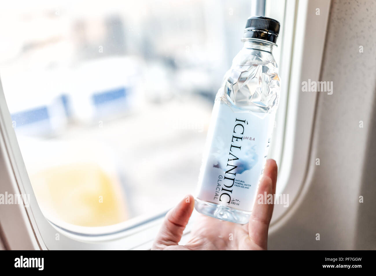 Dulles, USA - June 13, 2018: Young woman's hand holding Icelandic Glacial mineral water bottle in Icelandair airplane by window with view of airport i - Stock Image