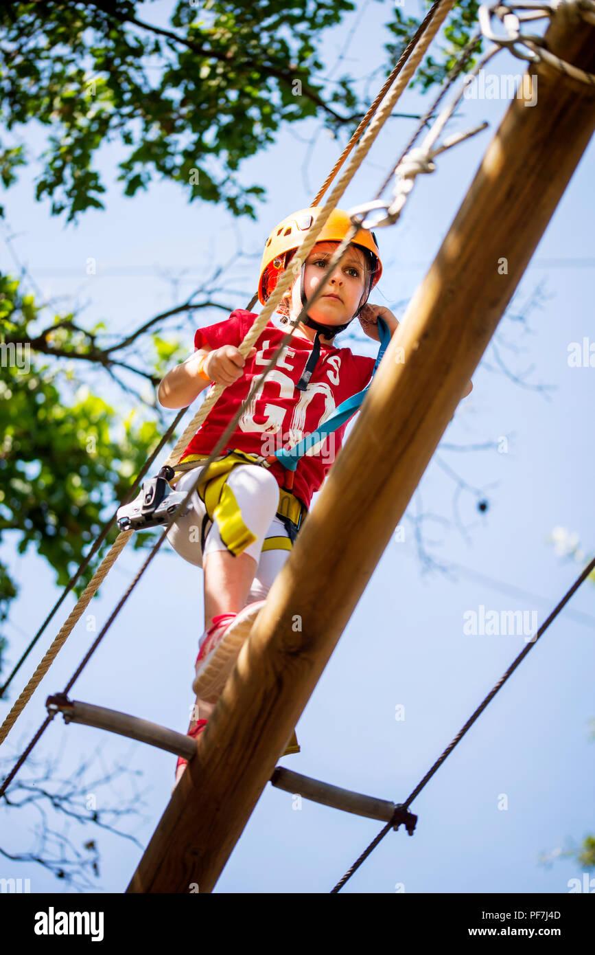 Little brave caucasian girl at outdoor treetop climbing adventure park - Stock Image