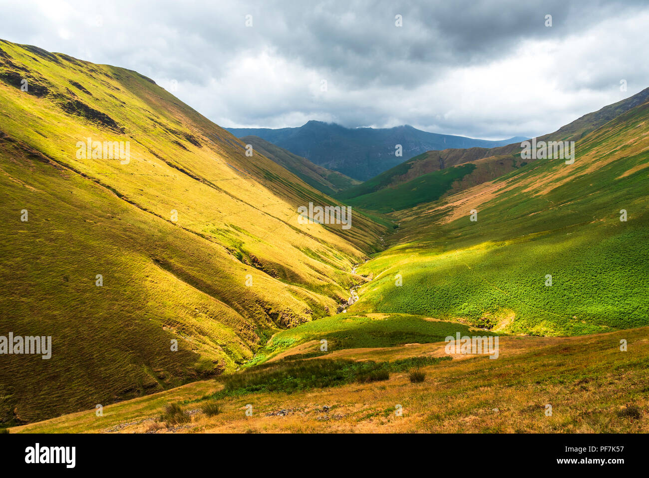 View down Sail Beck above Buttermere with a shadowy High Stile range on the skyline - Stock Image