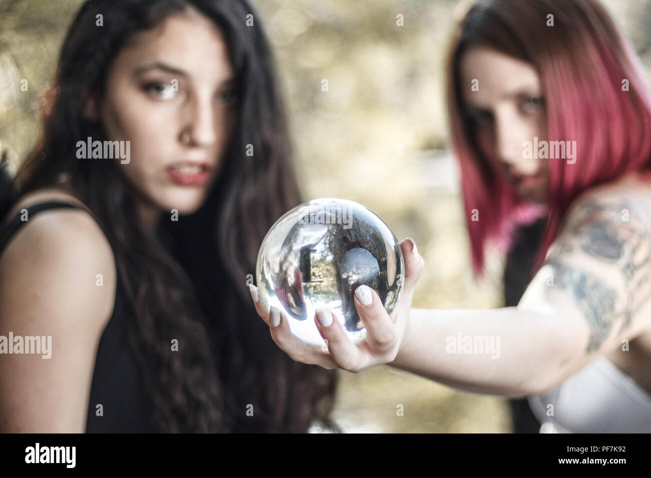Two girls dressed in black and white are predicting the future with a crystal ball at the pier of a forest. - Stock Image