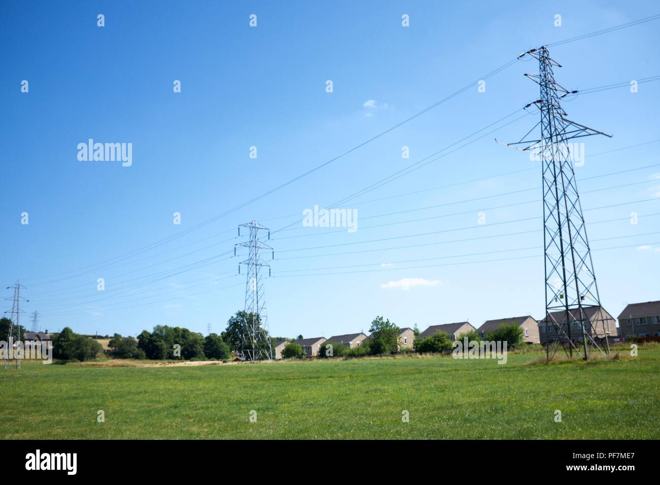 Pylons tower over a housing estate in New Mills,  High Peak,  Derbyshire - Stock Image