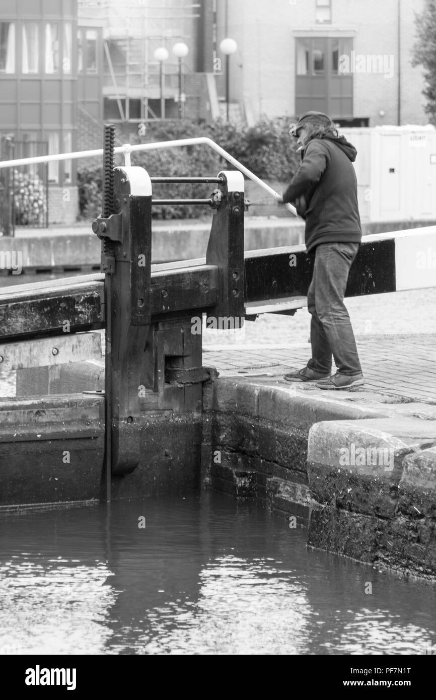 Black and white image of a man winding the mechanism to open sluice gates on the lock at City Road Basin, Islington, London, UK - Stock Image