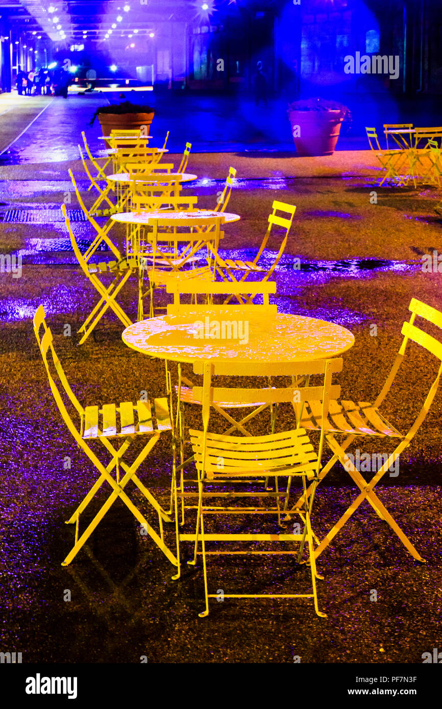 Unoccupied yellow-painted metal tables and chairs in the rain at night, King's Cross, London, UK - Stock Image