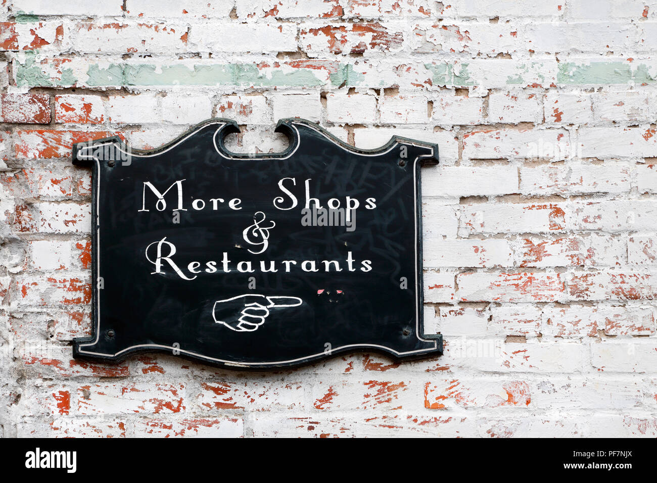 More shops and restaurants sign on old white brick wall Stock Photo