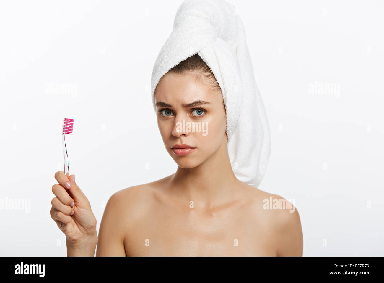 Serious pretty woman brushing her teeth on white background - Stock Image