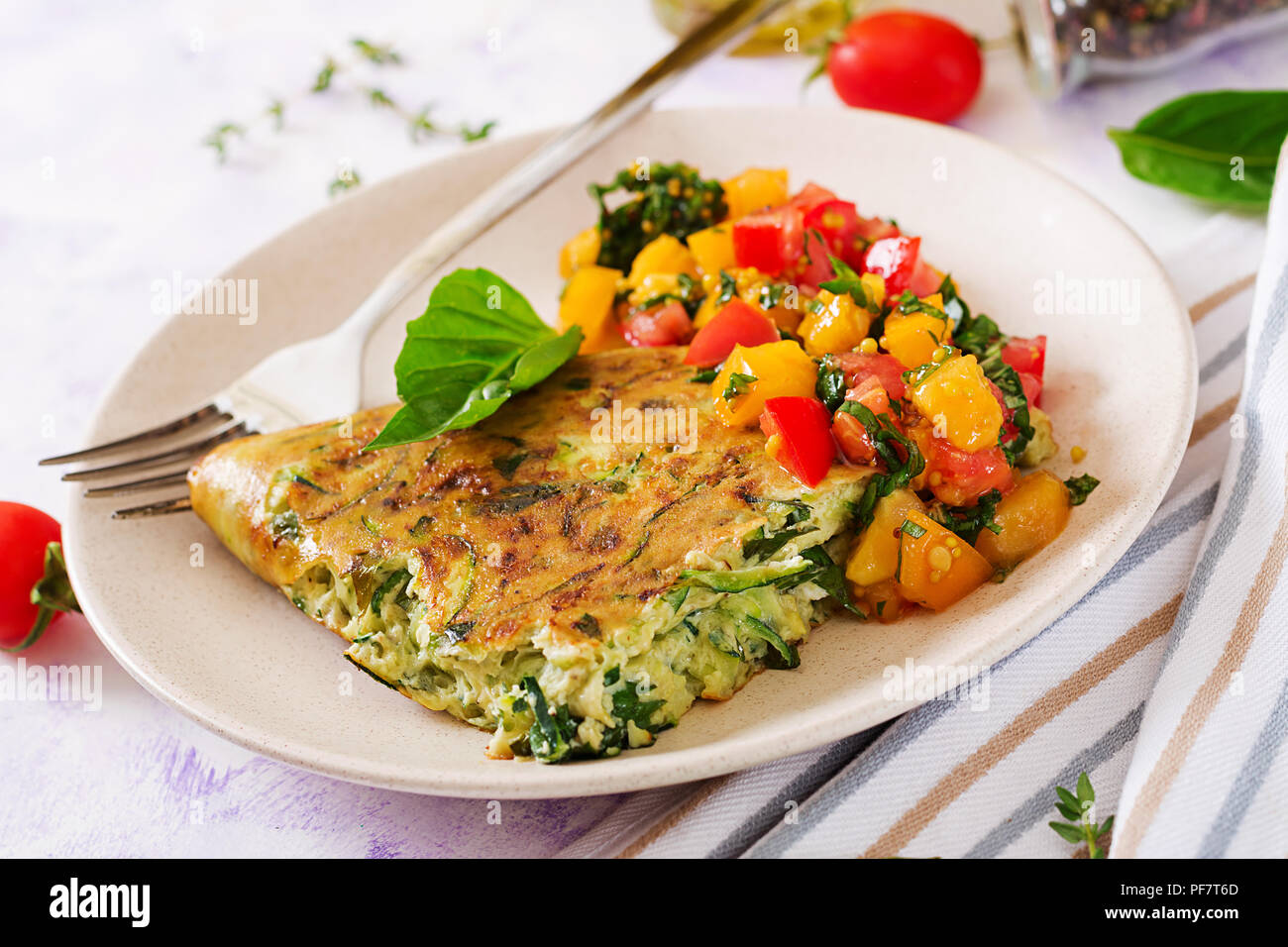 Frittata with zucchini, cheese, basil and salsa from tomatoes. Useful breakfast. Italian omelette. - Stock Image