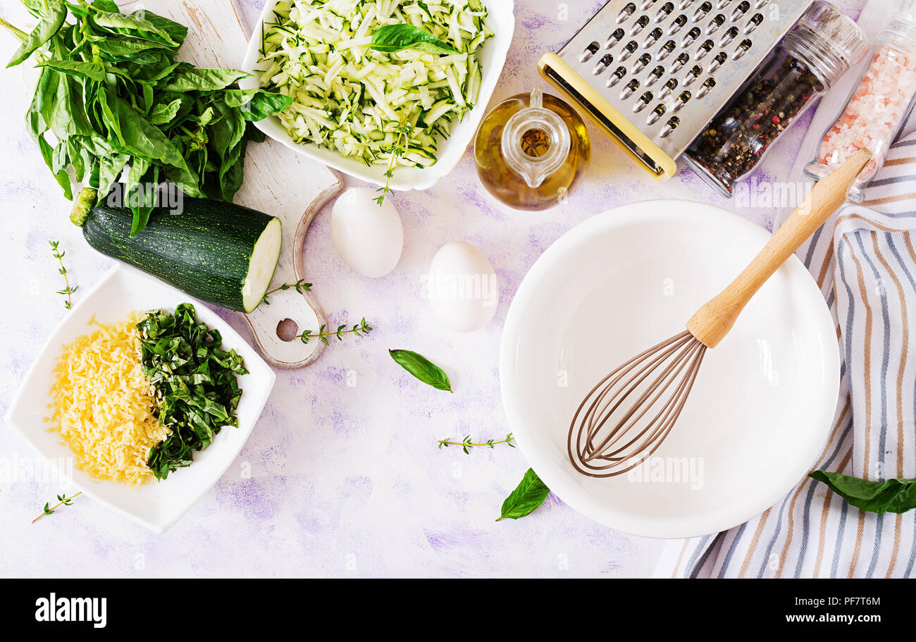 Ingredients for cooking frittata with zucchini, cheese and basil. Useful breakfast. Italian omelette. Top view. Flat lay. - Stock Image