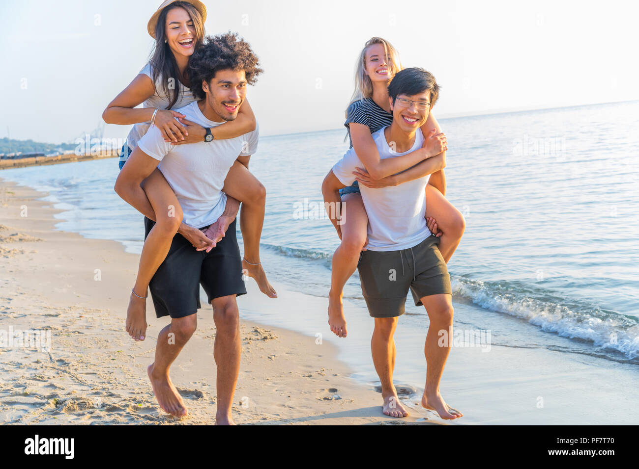 Group of friends walking along the beach, with men giving piggyback ride to girlfriends. Happy young friends enjoying a day at beach Stock Photo