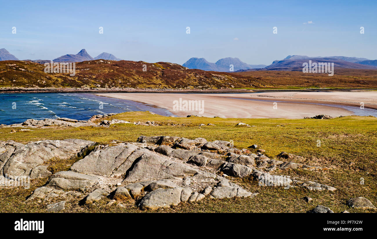 View across empty remote white sand beach of Achnahaird Bay, Scottish Highlands, to Stac Pollaidh, Beinn an Eoin and Ben More Coigach on the horizon. - Stock Image
