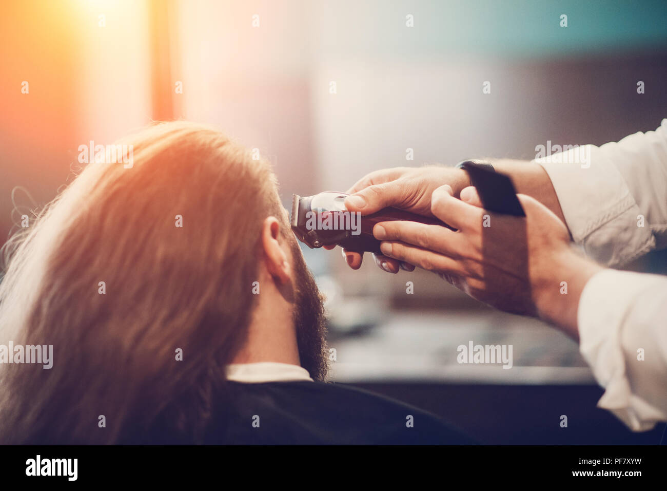 Hairdresser make hairstyle. Bearded model man and barber hand with razor trimmer and comb. - Stock Image