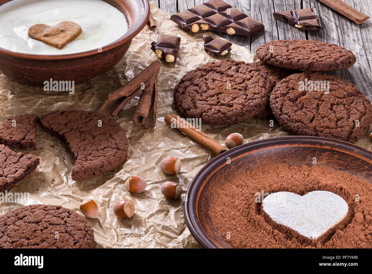 Chocolate cookies, chocolate with hazelnuts on a parchment paper, close-up - Stock Image