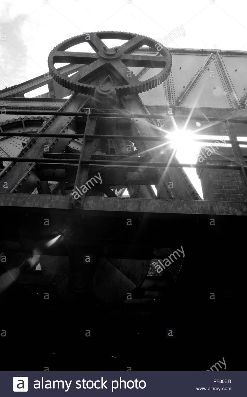 Old train track draw bridge mechanism with sunstar - Stock Image