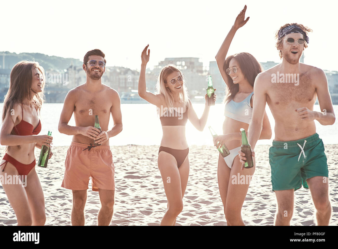 Enjoying carefree time with friends. Cheerful young people spending nice time together while sitting on the beach and drinking beer - Stock Image